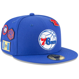 on the front of the philadelphia 76ers 2018 nba draft fitted cap is the philadelphia 76ers logo embroidered in white, red, and blue