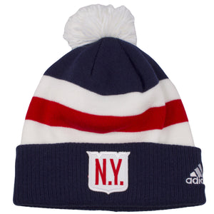 The front of this New York Rangers winter beanie hat has the New York Ranger shape logo on the front but has the letters N.Y. in red on top of the white logo. The base of this New York winter beanie hat has white and red stripes across from it. The fluffy pom right on top is white that matches the red white and blue color theme around this hat. The Adidas logo is embroidered on the left side of this beanie.