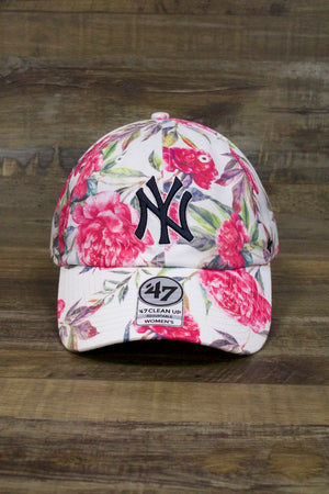 on the front of the New York Yankees Floral Womens Dad Hat | 47 Brand Peony White Baseball Cap is a dark blue Yankees logo and lots of flowers