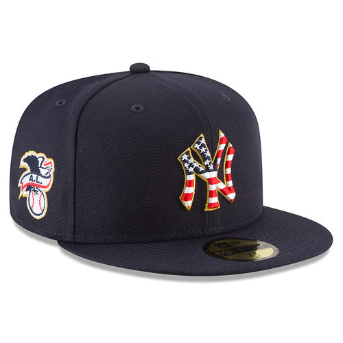 on the front of the new york yankees 2018 fourth of july fitted cap is the new york yankees logo embroidered with the stars and stripes pattern in red, white, and blue. On the wearer's right side is the American League logo embroidered in navy blue, white, and red