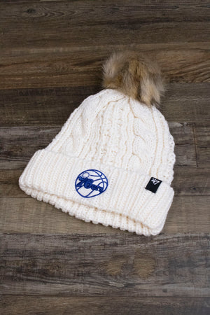 the front of the Philadelphia 76ers Ladies Fur Pom Cream Winter Beanie | Sixers Meeko Faux Fox Fur White Pompom Beanie has a tonal Sixers blue and white logo