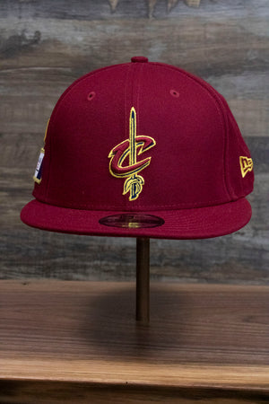 the front of the Cleveland Cavaliers Red NBA Draft Snapback Hat | Maroon 2018 On Court 9Fifty Snap Back has an XL Cavaliers logo with the sword on it