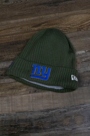 the front of the New York Giants 2018 Salute to Service Cuff Winter Beanie | NY Giants NFL On Field Olive Green Military Inspired Skullcap has a NY logo in blue