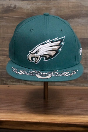 the Philadelphia Eagles NFL Draft 2019 Snapback Hat | Philly Eagles Midnight Green 9Fifty Snapback Draft Hat has an XL Eagles logo on the front and a Philadelphia Maneto slogan in latin on the brim