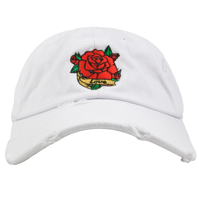 Embroidered on the front of the white rose blossom distressed dad hat is an image of a Rose above a banner of the word love