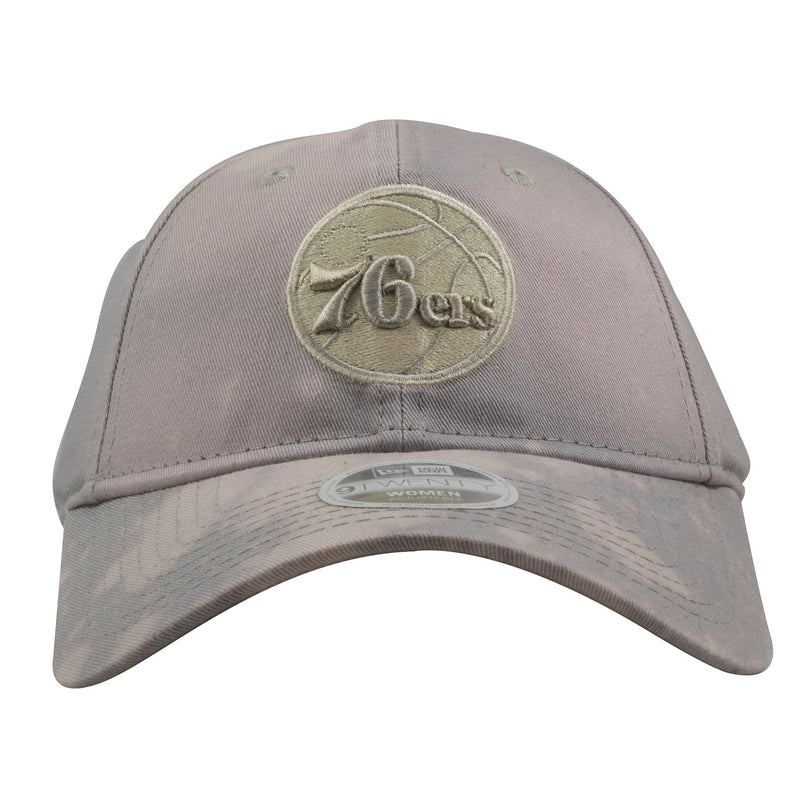 embroidered on the front of the Phialdelphia 76ers women's gray bleached dad hat is the 76ers logo embroidered in khaki