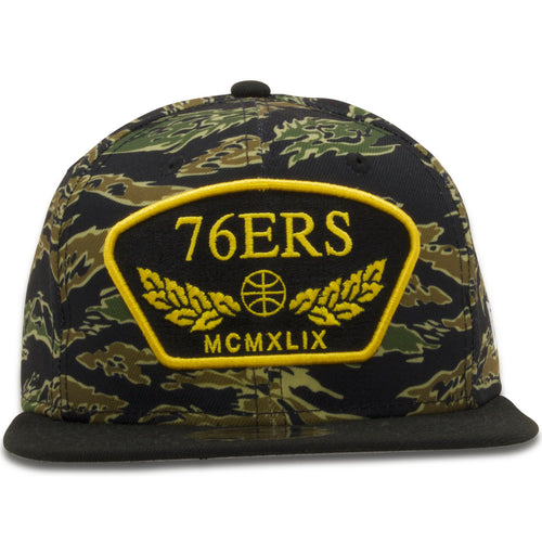 The crown of the Philadelphia 76ers camo snapback hat features a Tiger Stripe camouflage, on the front of the cap a black and gold patch is embroidered featuring the word 76ers, a basketball, laurel leaves and the year the team was established