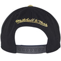 Mitchell and Ness embroidered in gold is seen on the back of Golden State Warriors black hat.
