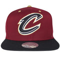 This Cleveland Cavaliers snapback hat is a maroon cap with black bill. The Cavaliers logo is embroidered in white and black with gold outlining.