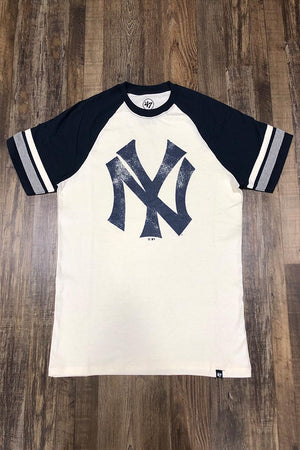 on the front of the New York Yankees Throwback Vintage 2-Tone T-Shirt | Distressed Yankees Logo Cooperstown Collection Heritage Opener Tee is a worn navy blue Yankees logo and pitcher stripe sleeves