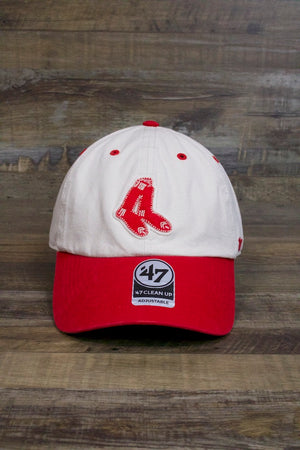 on the front of the Boston Red Sox Dad Hat | Cooperstown Collection Vintage Fuzzy Logo Bone and Red Baseball Cap is a patch with red socks and a red curved brim