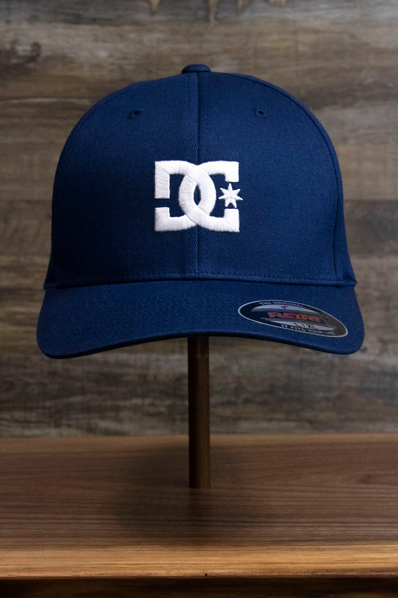 the front of the Navy Blue Skater Hat | DC Shoes Blue Bottom Navy Flexfit Cap is made of navy blue twill and has a white embroidered DC logo on it