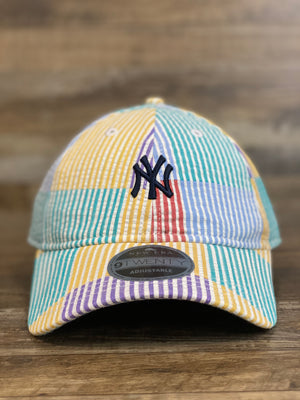 on the front of the New York Yankees Multi Collage Seersucker Dad Hat is a small navy blue New York Yankees logo
