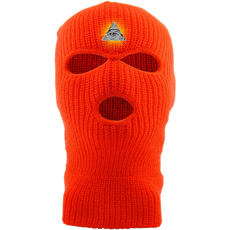 Embroidered on the forehead of the safety orange pyramid ski mask is the all seeing eye logo embroidered in white, black, and gold