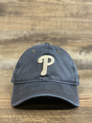 on the front of the Philadelphia Phillies Black Label Waxed Cotton Navy Blue Dad Hat is a cream colored Phils P logo