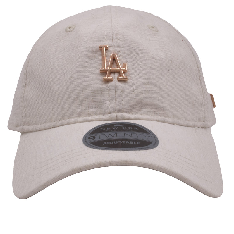 on the front of the los angeles dodgers oatmeal heather rose gold metallic dad hat has a los angeles dodgers logo in rose gold metal
