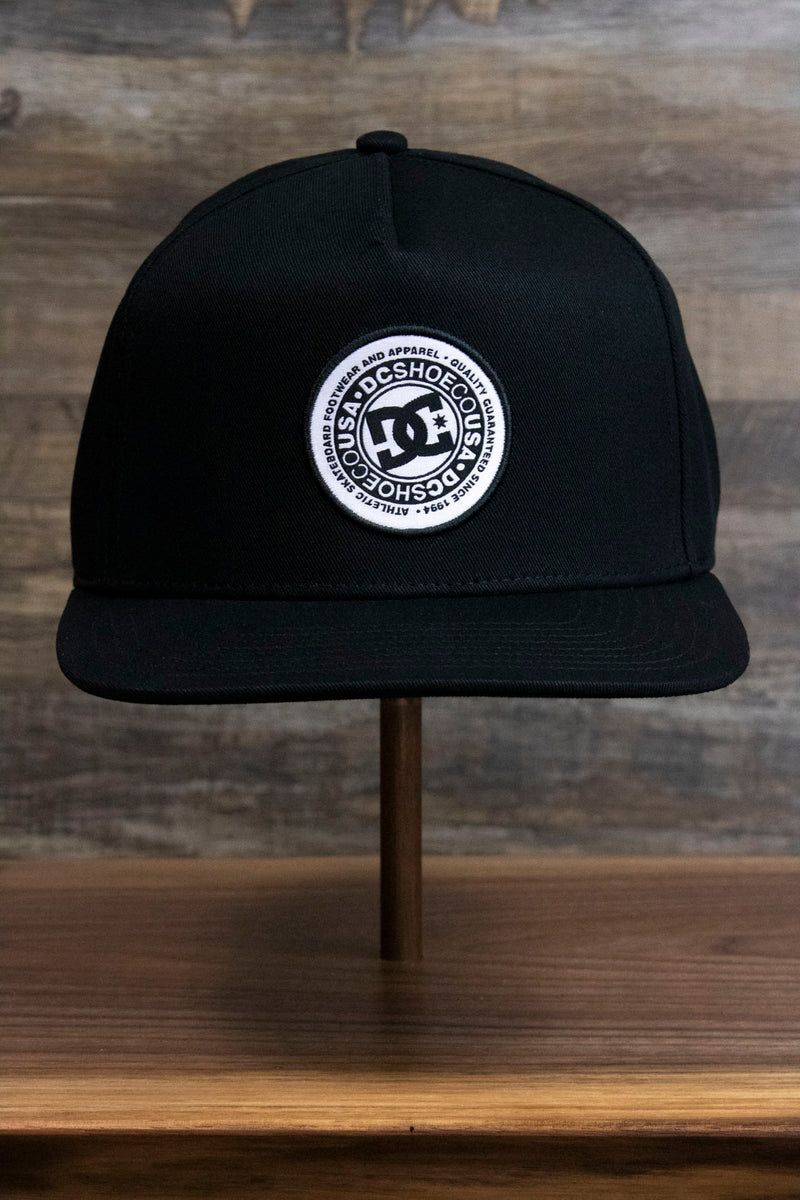 the Black Circle Patch Snapback Skater Hat | DC Shoes Black Bottom Snap Back Cap has a circular emblem on the front