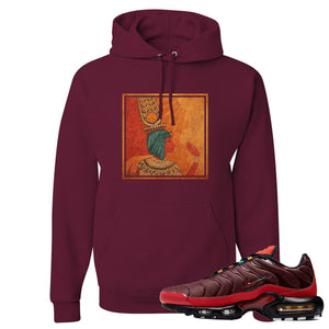 printed on the front of the air max plus sunburst sneaker matching maroon pullover hoodie is the vintage egyptian logo