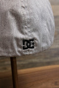 the Light Gray Bentbrim Skater Hat | DC Shoes Black Bottom Heather Gray Flexfit Cap has a tiny black DC logo on the back