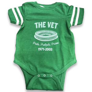 printed on the front of the veteran stadium pride pretzel and prison kelly green onesie is the vet logo printed in white