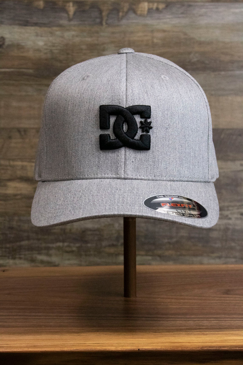 the Light Gray Bentbrim Skater Hat | DC Shoes Black Bottom Heather Gray Flexfit Cap has a black DC logo on the front