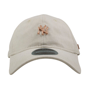on the front of the new york yankees oatmeal dad hat is the yankees logo in rose gold metal