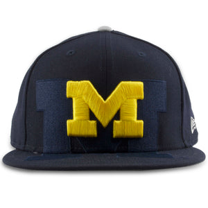 The University of Michigan Overspill snapback hat is solid navy blue with the Michigan logo embroidered on the front in yellow