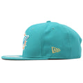 A golden New Era flag logo is shown on the left side of this Miami Dolphin snapback cap.