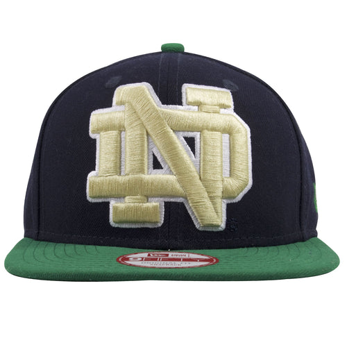 on the front of Notre Dame snapback hat is a Notre Dame logo embroidered in tan and white