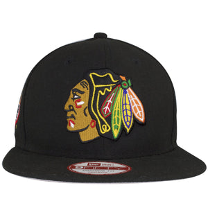 on the front of the chicago blackhawks 6x stanley cup champions snapback hat is the chicago bulls logo embroidered in tan, black, yellow, red, green, and blue.