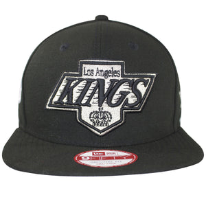 on the front of the los angeles kings 2x stanley cup champions snapback hat is the los angeles kings vintage logo embroidered in gray and black