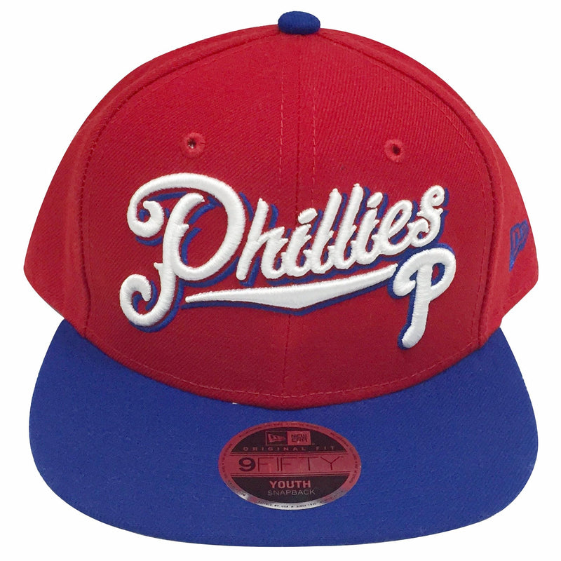 on the front of the philadelphia phillies red on blue snapback hat is a white philadelphia phillies logo and phillies script written in white thread
