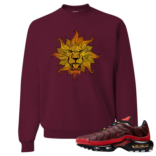 printed on the front of the air max plus sunburst sneaker matching maroon crewneck sweatshirt is the vintage lion head logo