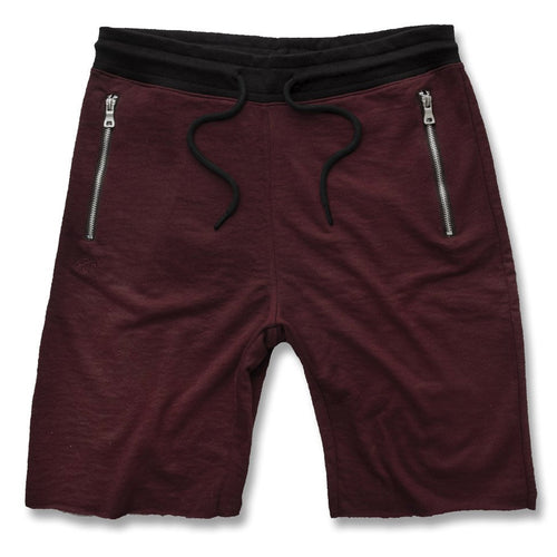 the wine maroon jogger sweatshorts are solid maroong with a black waistband, black adjustable strings and zippers on the pockets with metal hardware