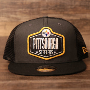 The front side of the gray/black Steelers 9fifty mashback snapback trucker cap for the NFL Draft 2021.
