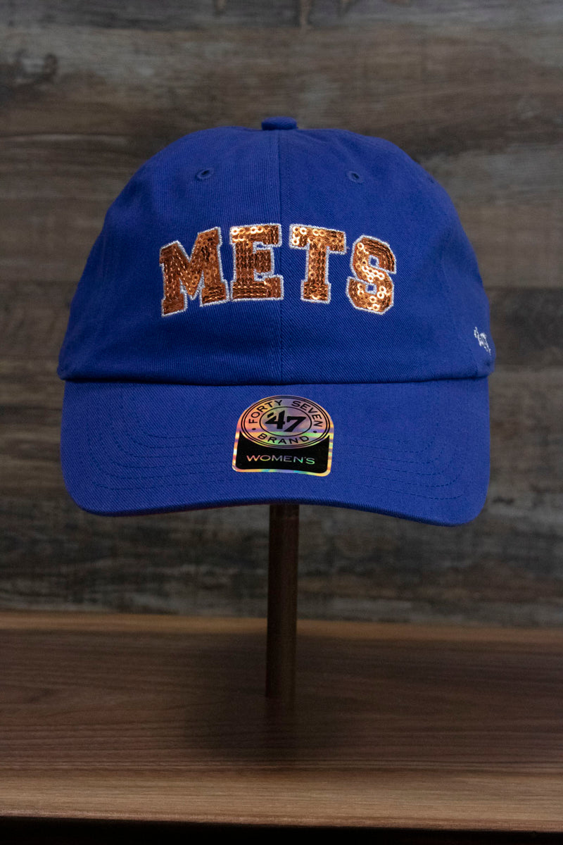 the front of the New York Mets Sequin Lettering Blue Womens Baseball Hat | Ladies Royal Blue Mets Baseball Hat with Sequins has the Mets logo in gold orange sequins