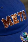the New York Mets Sequin Lettering Blue Womens Baseball Hat | Ladies Royal Blue Mets Baseball Hat with Sequins has a complex sewn on pattern of sequins on the front that spells out the METS wordmark