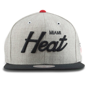 The Miami Heat snapback hat features a heather gray structured crown, a black flat brim and the Miami Heat script embroidered in black