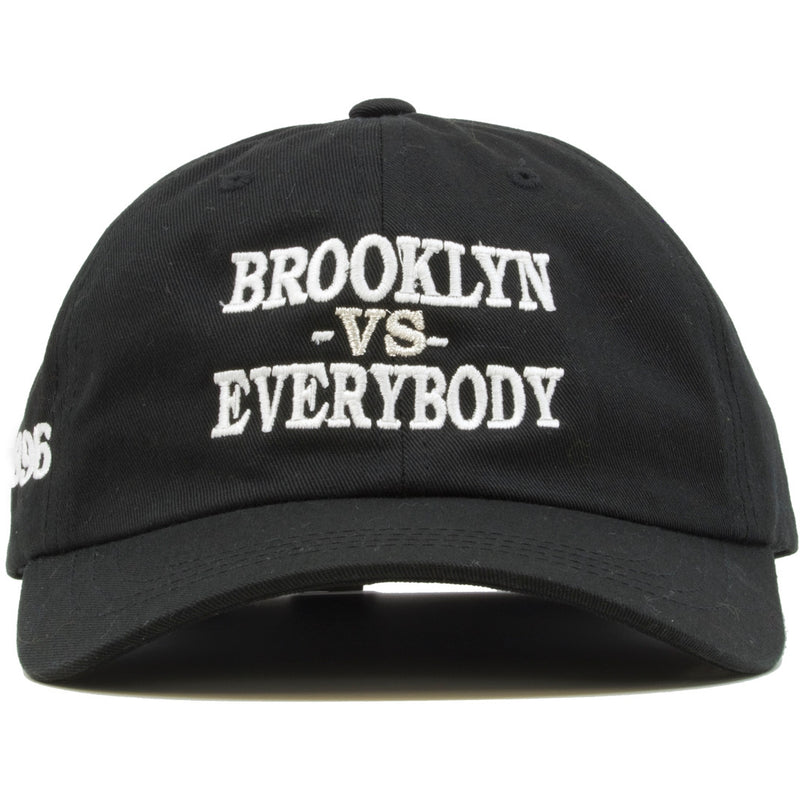 "The front of the Brooklyn vs Everybody dad hat is solid black and has the words ""Brooklyn vs Everybody"" embroidered on the front in white stitches."