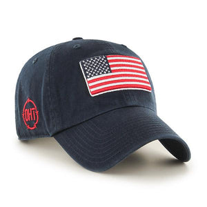 Embroidered on the front of the USA Flag Operation Hat Trick Navy Blue Adjustable Baseball Cap is the USA flag embroidered in red, white, and blue. On the right side of the OHT navy blue baseball cap, the Operation Hat Trick logo is embroidered in red