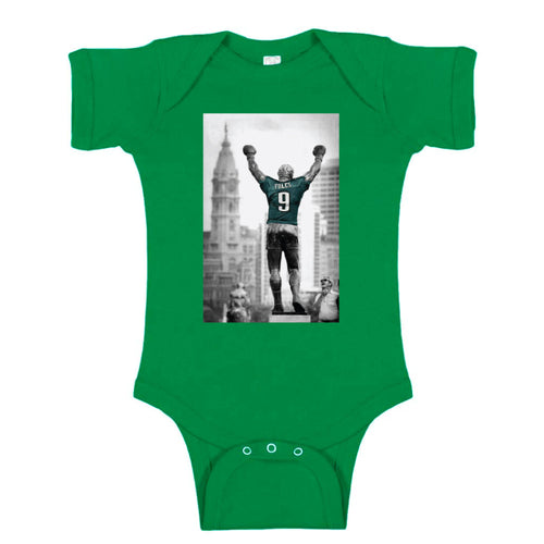 on the front of the baby rocky statue nick foles philadelphia eagles kelly green onesie is a photograph featuring the rocky statue wearing a nick foles jersey