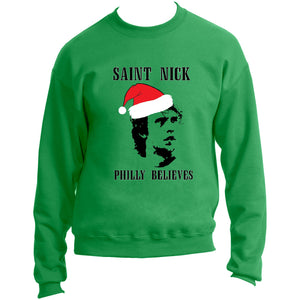 "on the front of the kelly green saint nick crew neck is an image of nick foles with a santa hat and the lettering ""Saint Nick Philly Believes"""