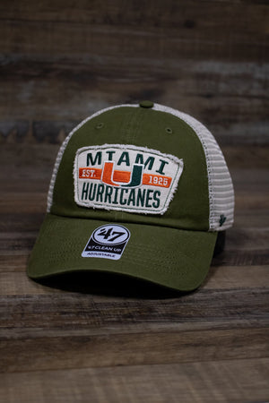 "on the front of the Miami Hurricanes mesh back dad hat is a distressed vintage embroidered patch with the University of Miami logo, Established 1925, and the words ""Miami Hurricanes"" on it"
