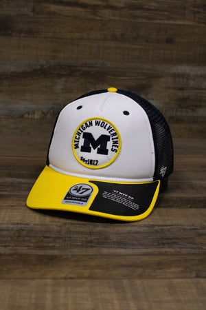 on the front of the Michigan Wolverines mesh back trucker hat is a yellow brim, a white crown, and a circular embroidered patch with the letter M logo, Established 1817, and Michigan Wolverines written on it