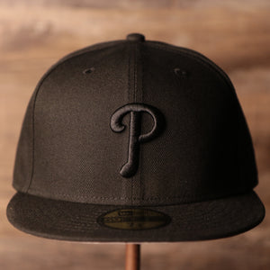 The front side of the black on black Philadelphia Phillies 59fifty by New Era.