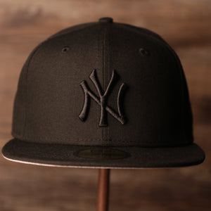 The front of the black on black 59fifty has the black logo of the New Yankees.