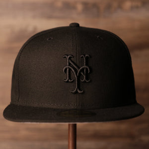 The front of the black on black 59fifty has the black logo of the NY Mets.