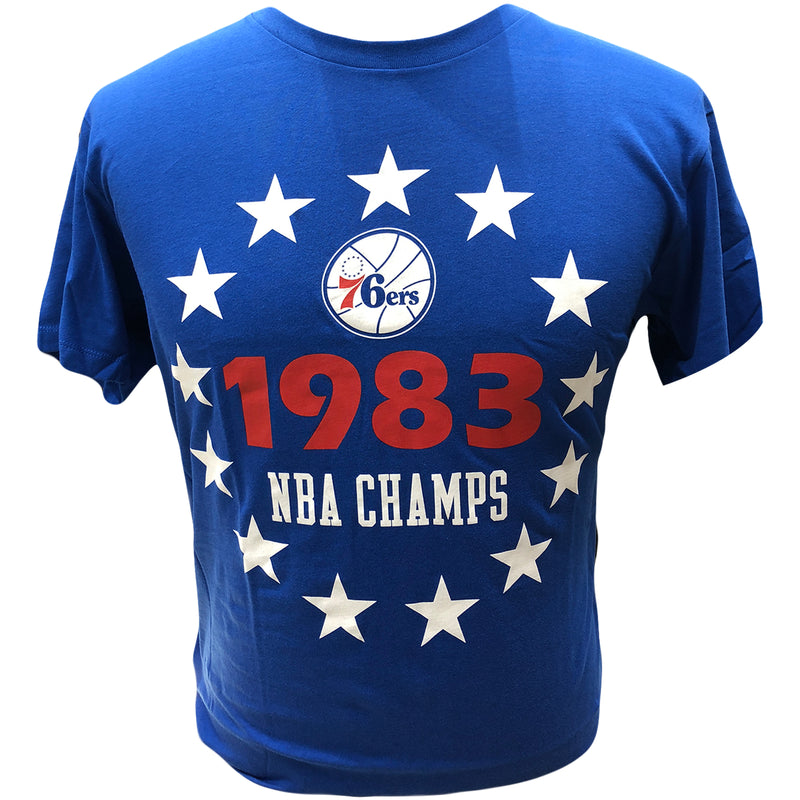 Printed on the front of the Philadelphia 76ers 1983 NBA Champs Royal Blue t-shirt is the 76ers logo, the year 1983 in red and the words NBA CHAMPS in white. Surrounding the front logo are 13 white stars