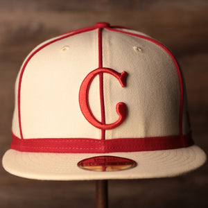 The front side of the cream Cincinnati Reds 59fifty by New Era with red pinstripes.