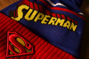 Superman Beanie | DC Comics Superman Comic Con Super Hero Winter Pom Beanie | OSFM the front of this beanie has the superman logo on the cuff and the wording on the top